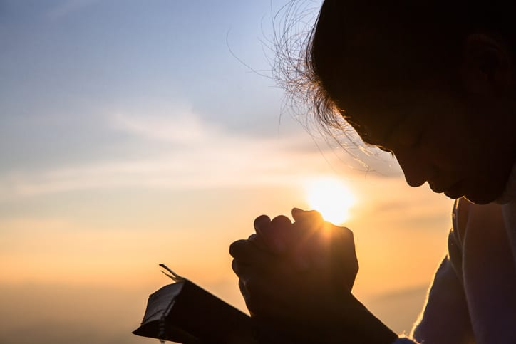 Silhouette of christian young woman praying with a  cross and open the bible at sunrise, Christian Religion concept background.